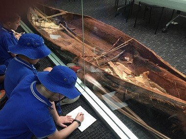 students sit and look at bark canoe