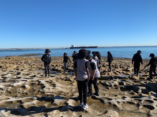 students on rock platform