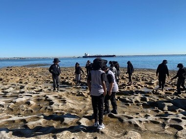students walk on rock platform at Botany Bay